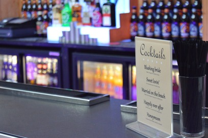 A wedding cocktail menu displayed on a mobile bar at a wedding venue in Suffolk