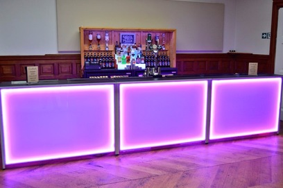 A complete mobile bar setup with LED bar units and back bar display with bottle fridges at a wedding in Essex
